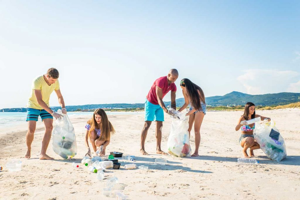 Friends cleaning the beach and collecting plastic to save marine life